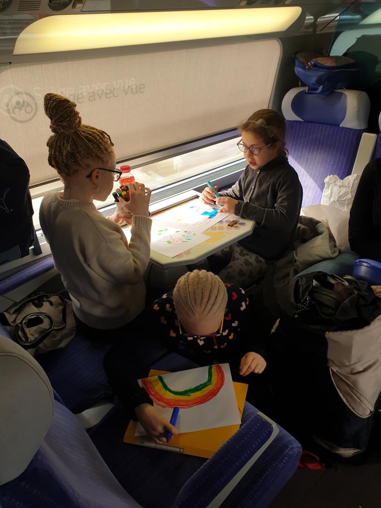 Des enfants font du dessin pendant le voyage en train