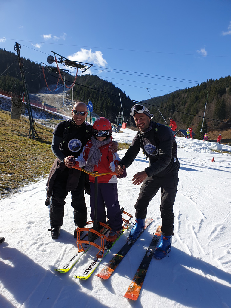 Un enfant et deux encadrants font du ski