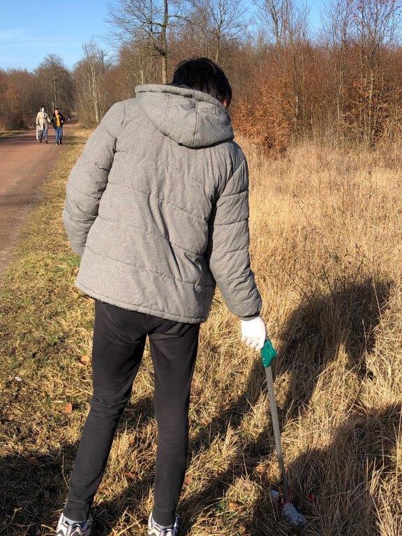 Un jeune ramasse un déchet avec une pince