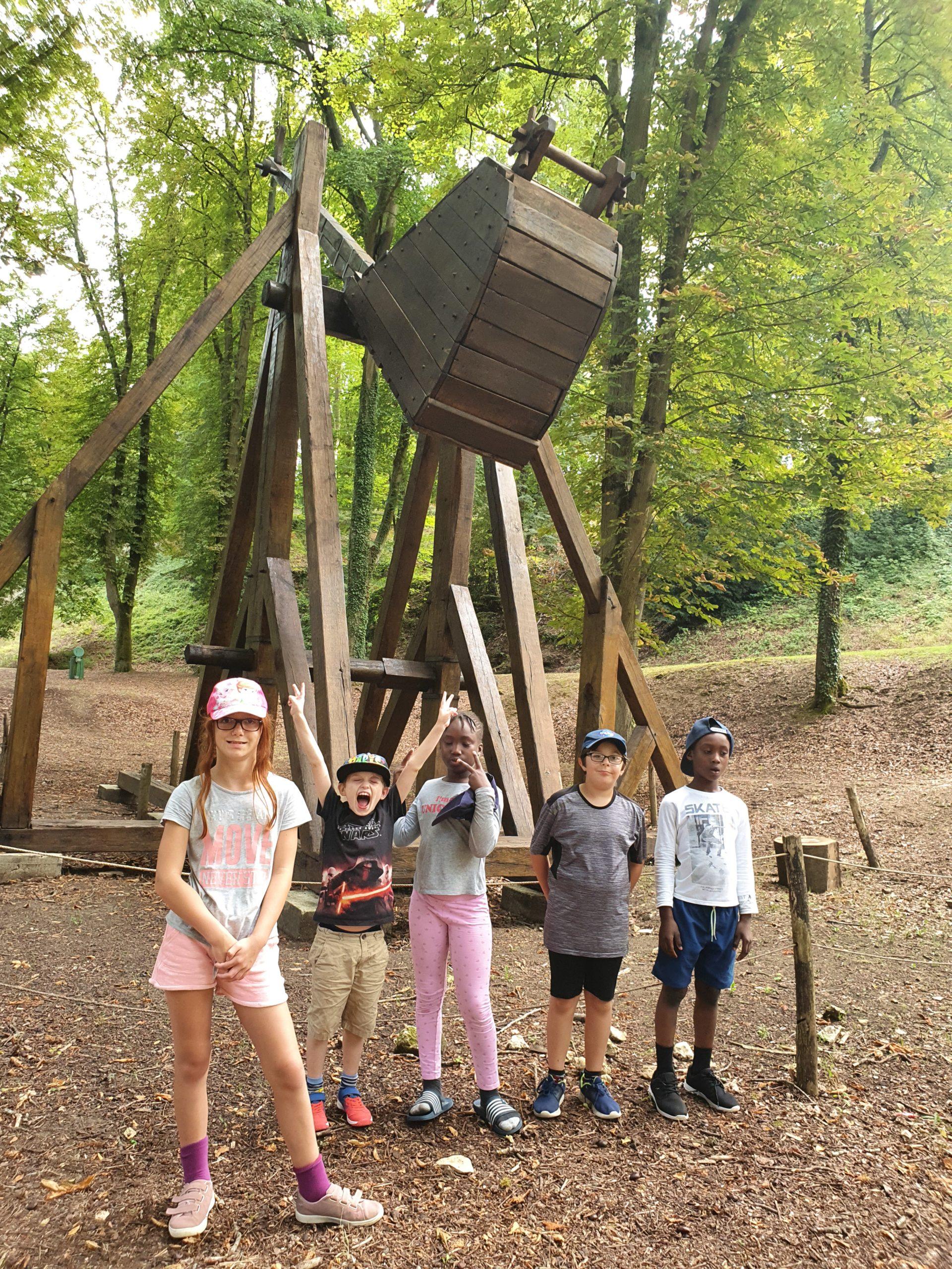 Des enfants devant une catapulte