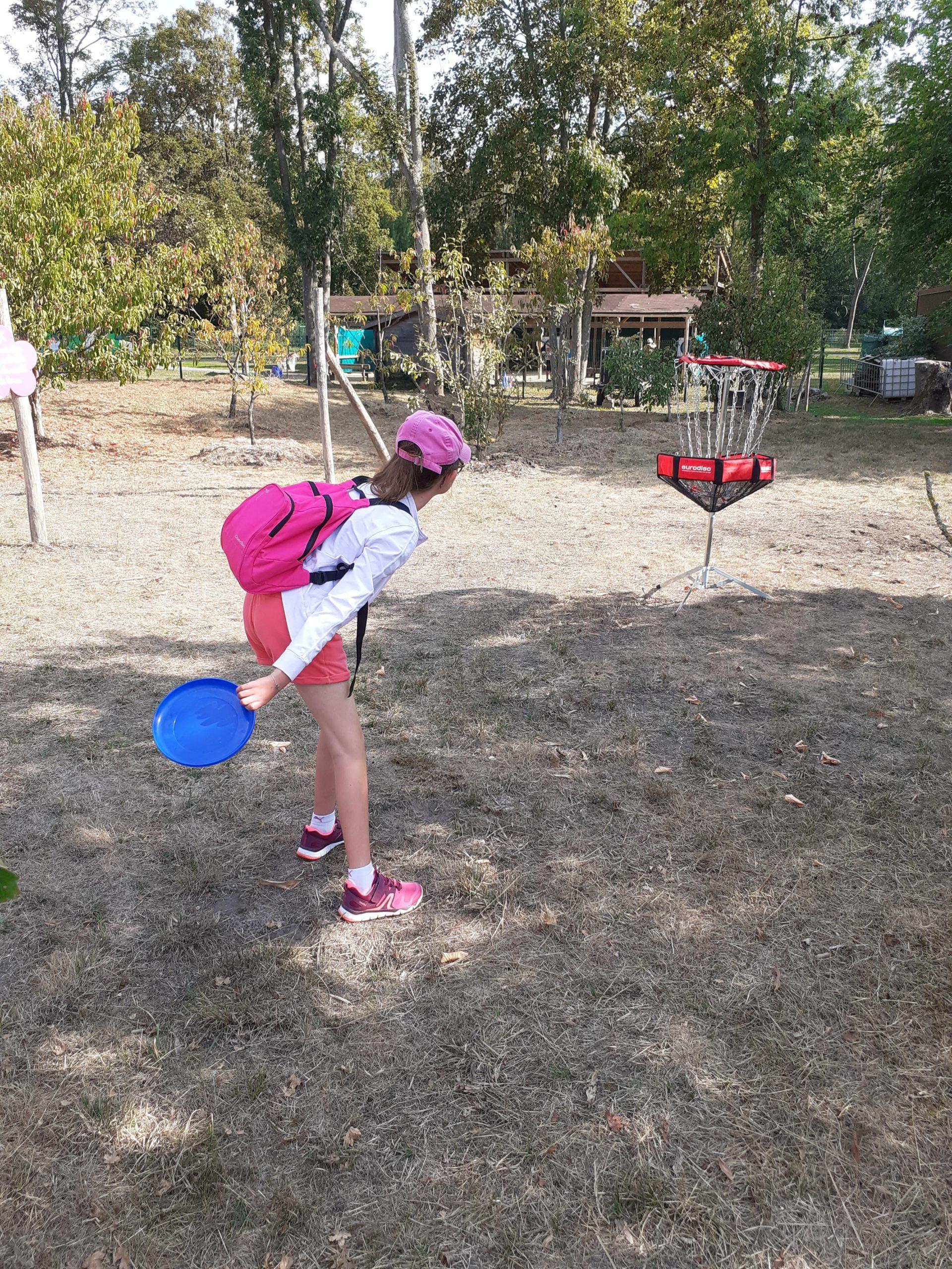 Une enfant lance un frisbee