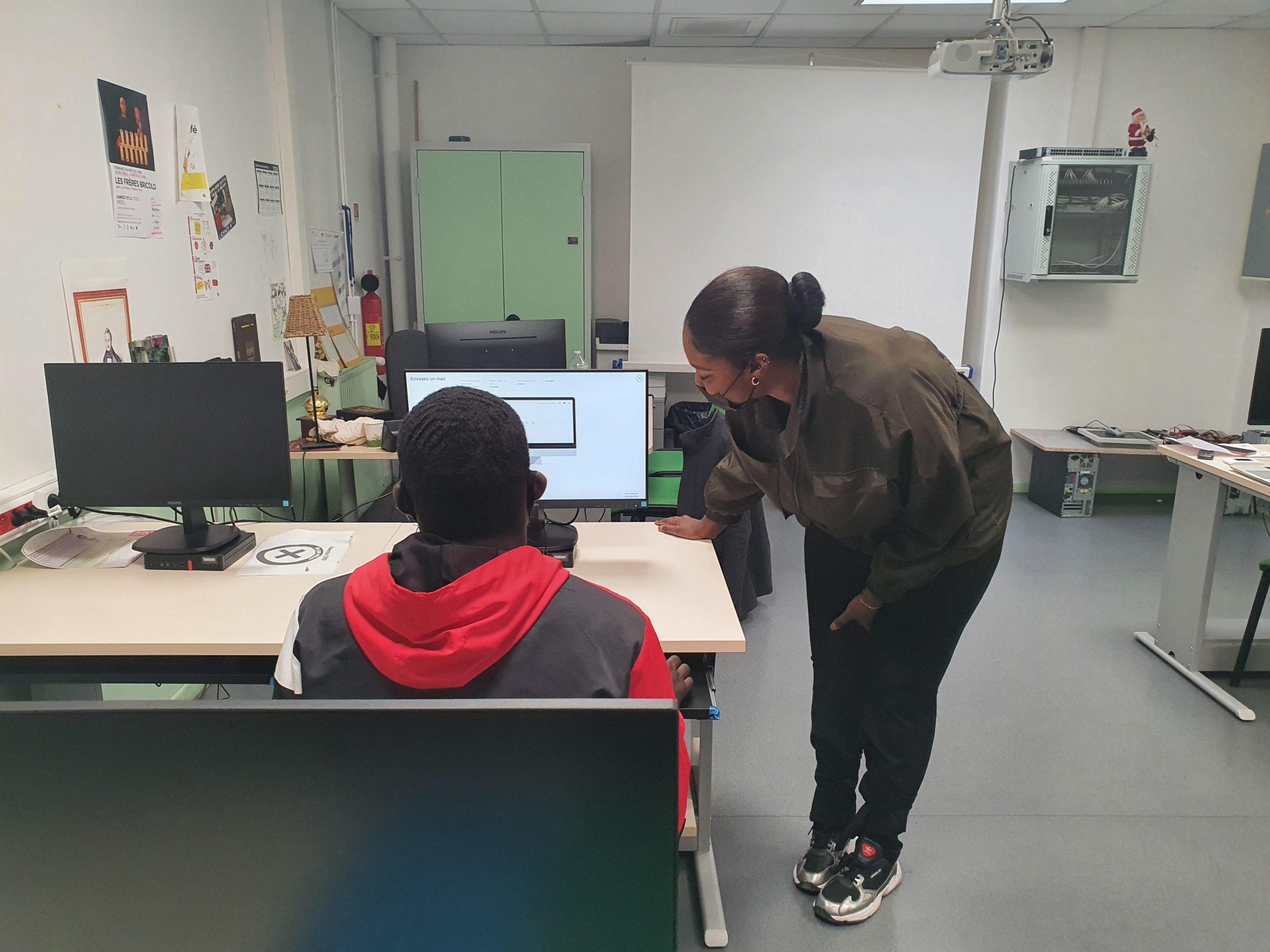 Une éducatrice explique à un jeune l'utilisation d'un ordinateur
