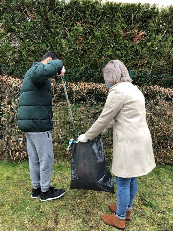 Un jeune dépose un déchet dans un sac avec une pince
