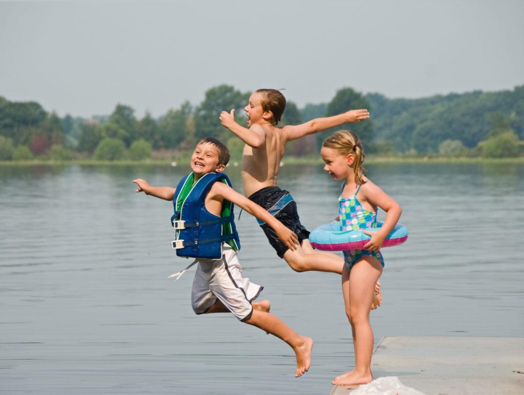 Trois enfants qui sautent dans l'eau